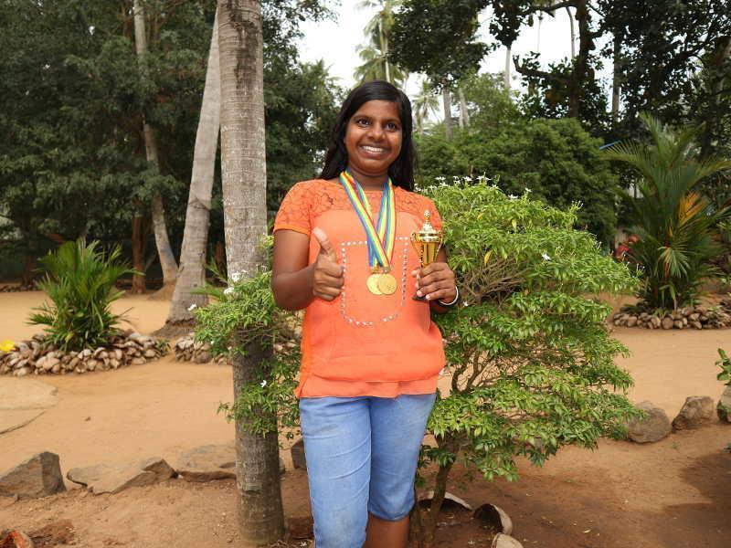 Shashikala ist stolz über ihre Medaillen und Trophäe.