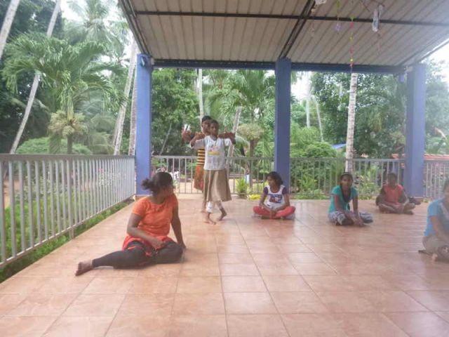 Madumali und Nipuni tanzen, alle anderen sitzen auf dem Boden