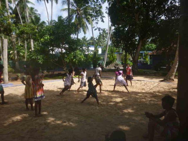 Man sieht ca. 10 Mädchen, die auf einem Volleyballfeld das Spiel Kaberti spielen.