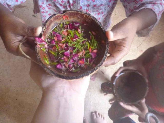 Man sieht die Hände eines Mädchens, die eine Kokosnussschale gefüllt mit Wasser und Blumen hält.
