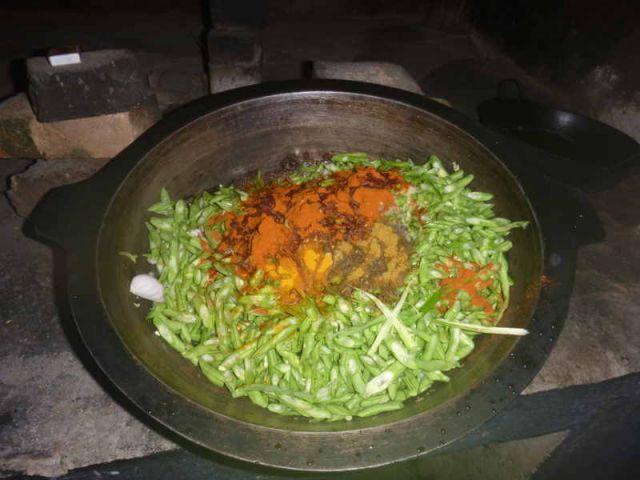 Man sieht einen Topf voller Bohnen, auf denen Gewürze, wie Chilipulver, zu sehen sind.