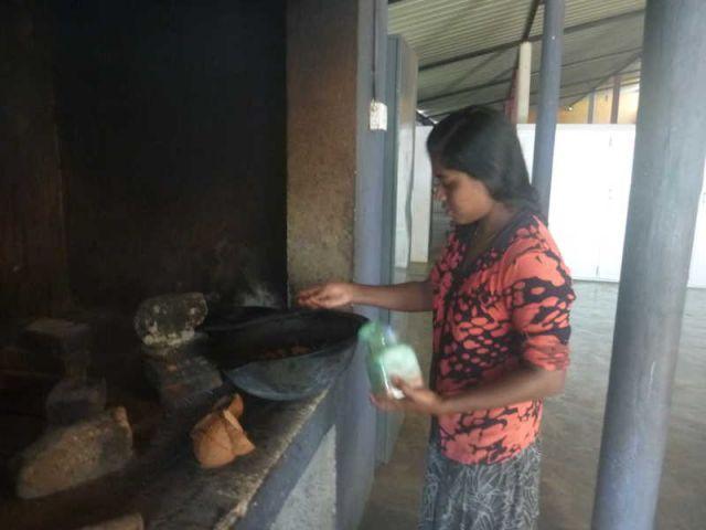 Nadeesha steht an der Feuerstelle und gibt Salz zum Curry.