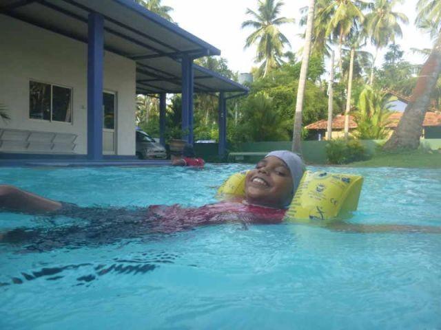 Man sieht das Mädchen Vishmika, die sich auf dem Wasser treiben lässt.