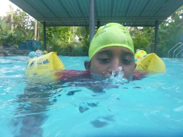 Man sieht das Mädchen Vindiya, die mit ihrem Mund im Wasser blubbert