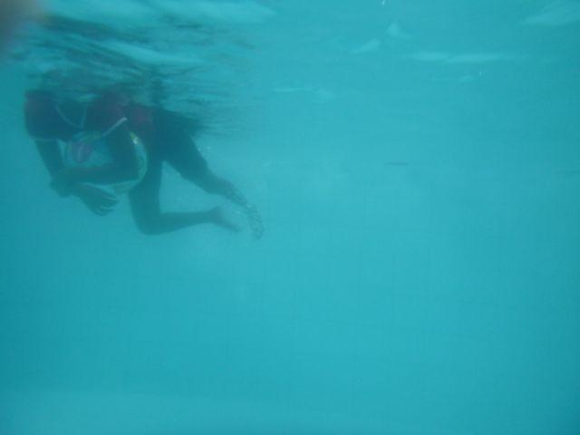 Das Bild wurde unter Wasser aufgenommen. Man sieht ein Mädchen, das einen Wasserball als Schwimmhilfe benutzt