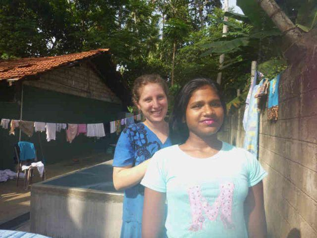 Man sieht das Mädchen Sandunika. Hinter ihr steht die Praktikantin Lisa und schneidet ihr die Haare.