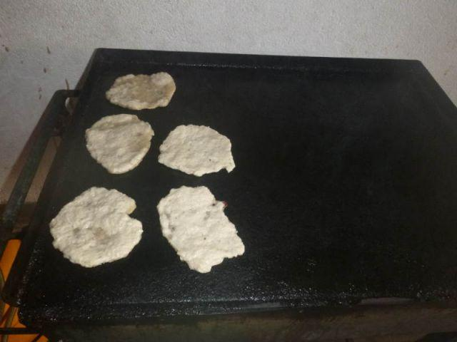 Man sieht Roti-Pfannkuchen, die gerade angebraten werden.