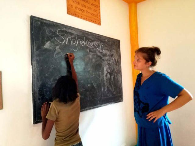 Subani als Lehrerin an der Tafel