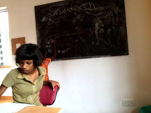 Man sieht Subani und Sachini im Klassenzimmer, während sie versuchen singhalesische Wörter zu erklären.