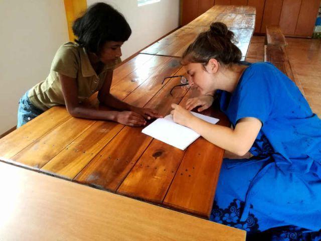 Man sieht Subani, wie sie mir beim schreiben auf singhalesisch zu schaut.