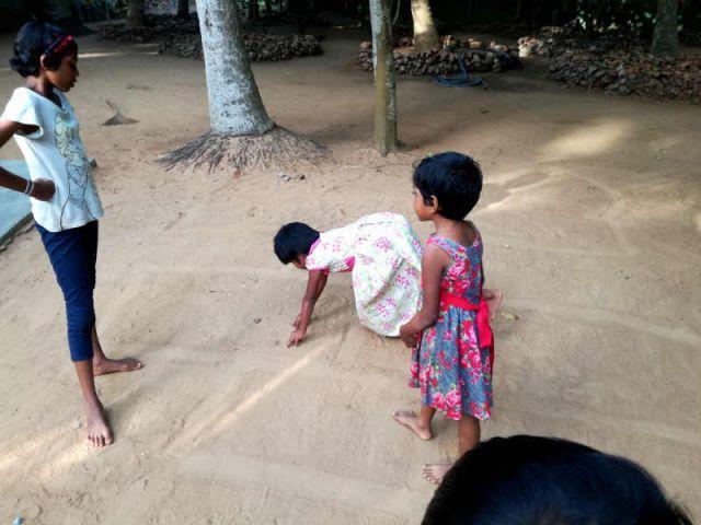 Man sieht drei Mädchen Hüpfekästchen spielen