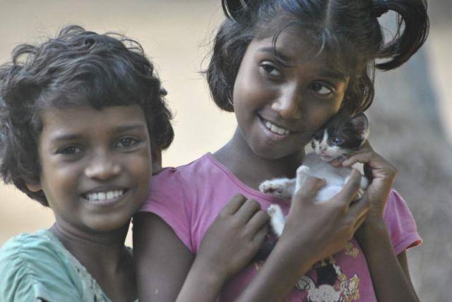 Man sieht Madushani und Achini mit einer kleinen Katze auf dem Arm