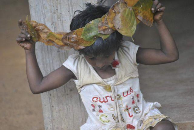 Man sieht Aruni wie sie sich eine Blätterkrone bastelt.