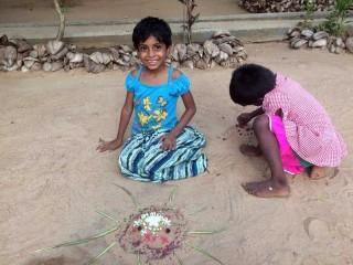 Dinithi und Aruni machen Sandkunst.